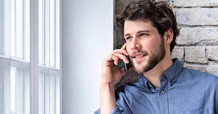 Mann mit Handy Imagemotiv Cloud-Telefonie MBCOM